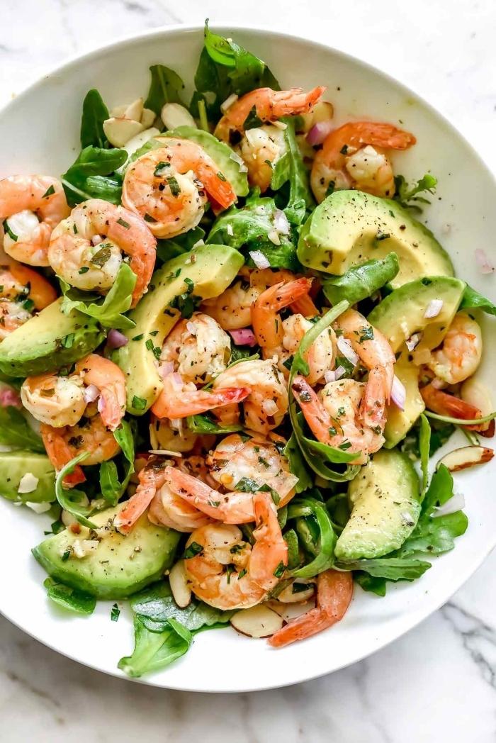 salade d'été originale aux crevettes sautées au citron, à l'avocat, roquette et aux épinards