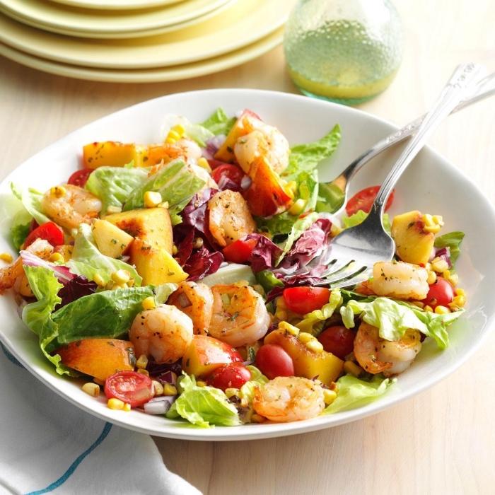salade estivale de laitue, crevettes, tomates cerises et pêches au goût de la méditerranée, assaisonnée avec de la vinaigrette à