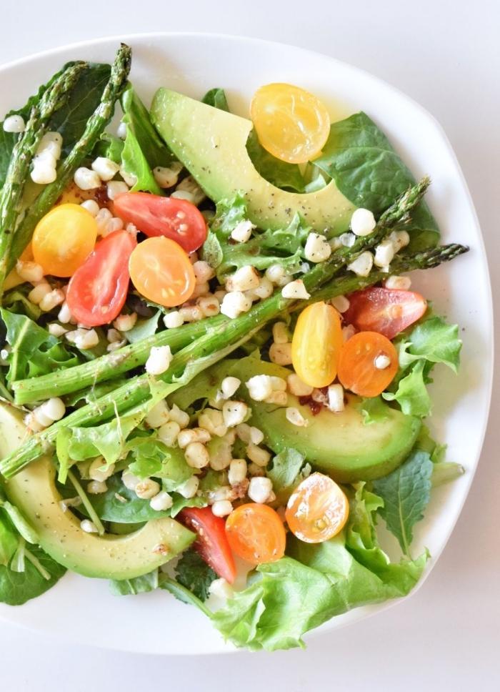 recette de salade composée été de chou kale, asperges, tomates cerises, tranches d'avocat et des graines de mais