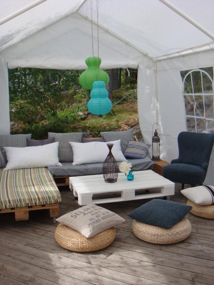 un salon de jardin entièrement réalisé avec des palettes avec petite table basse palette blanche, coin cozy dans le jardin avec des poufs ronds en rotin et une multitude de coussins