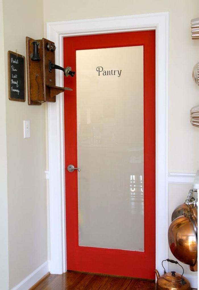 idée pour relooker une porte d'intérieur vitrée avec de la peinture, l'encadrement de porte rouge et blanc crée un joli accent coloré dans l'espace cellier