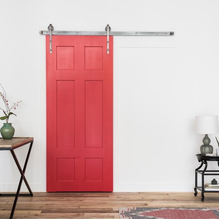 une porte interieur bois de grange repeinte en couleur corail en contraste avec la déco épurée et les murs blancs, une porte de grange remis au goût du jour grâce à quelques coups de peinture