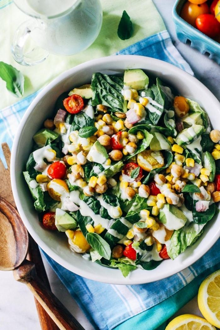recette salade été de maïs grillé, tomates cerises, pois chiches et d'épinards, servie avec de la sauce de salade au yaourt et au basilic