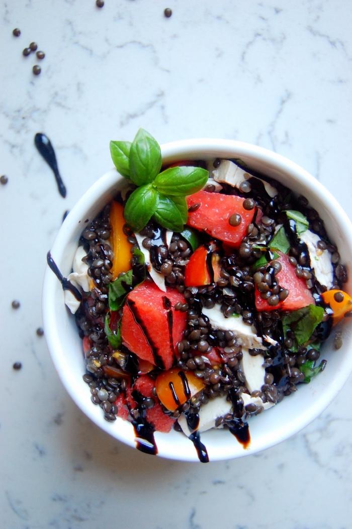 salade composée originale de tomates cerises fraîches, mozzarella, morceaux de pastèque et lentilles beluga, idée de repas léger et rapide pour l'été