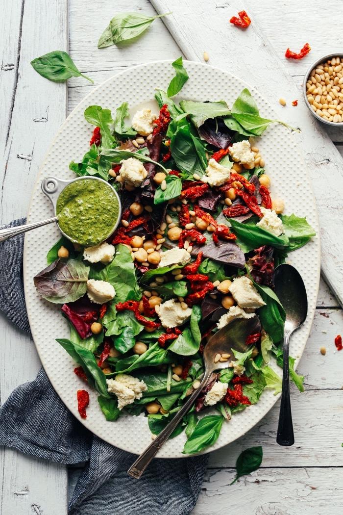 recette de salade verte composée d'épinards, tomates séchés, pois chiches servie avec de la ricotta végétale aux amandes et à la sauce pesto