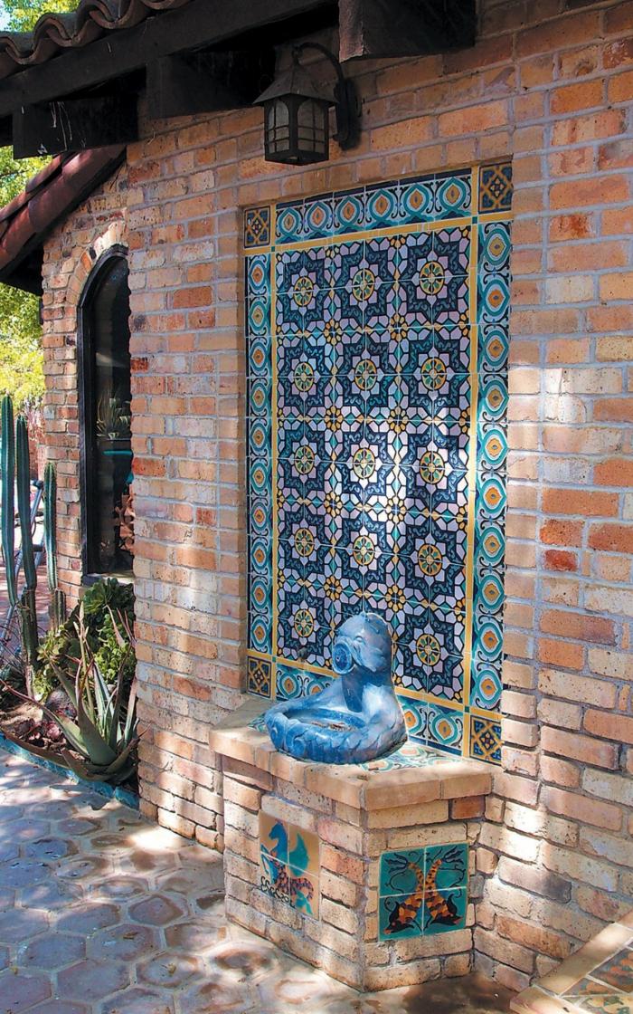 comment habiller un mur exterieur en mosaïque, éléments mosaïque en bleu, jaune et orange, composition insérée dans un mur en briques rouges, luminaire lanterne vintage, statuette en céramique bleu turquoise