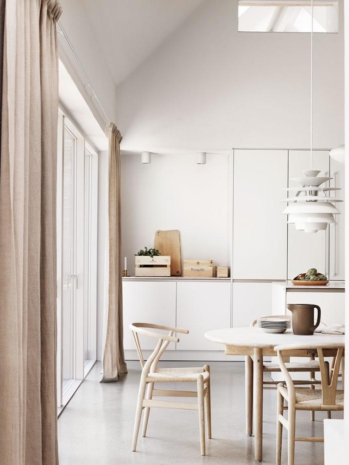 décoration de style minimaliste dans une cuisine blanche équipée de meubles blanc et bois avec rideaux longs beige