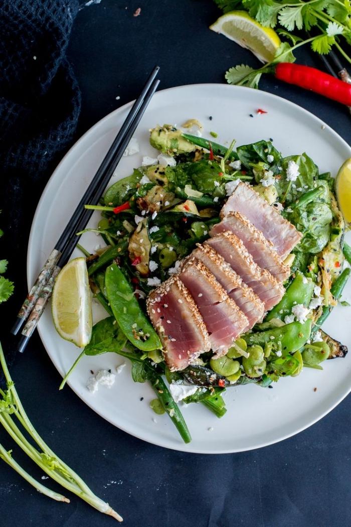 recette de salade verte composée inspirée de la cuisine asiatique, aux épinards, courgettes, pois mange-tout et avocat, servie avec du saumon mariné en croûte de sésame