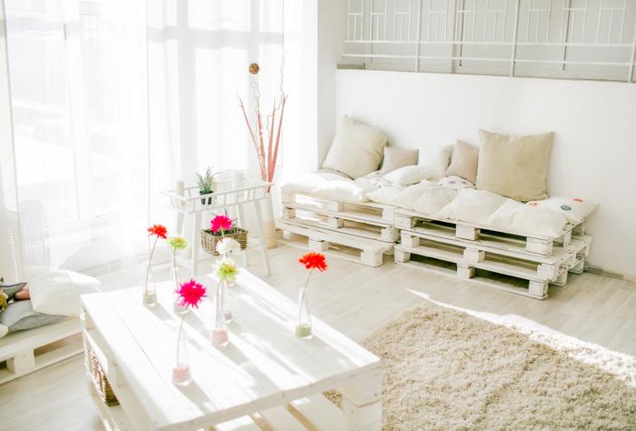 salon élégant et cosy tout blanc équipé de meubles palettes peints en blanc, table basse en palette qui s'accorde avec le canapé-lit