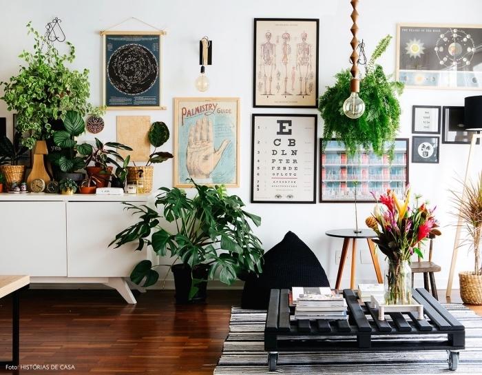une table basse palette avec roulettes à finition noir brillant d'aspect chic qui s'accorde avec la déco bohème vintage du salon aux accents en noir et en vert