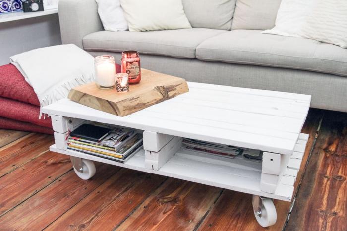 une table basse palette blanche sur roulette avec espace rangement, décorée avec un plateau en bois et des bougies pour une ambiance cocooning