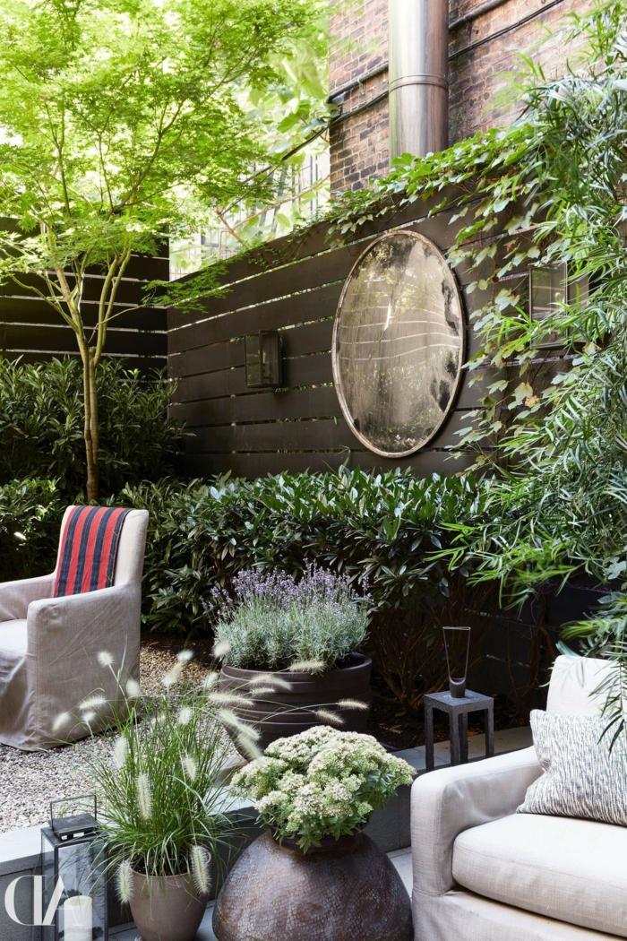 revetement mural exterieur, habiller un mur extérieur en bois marron et le décorer avec un grand miroir œil de sorcière rond, coin de jardin avec des fauteuils en tissu gris clair, comment habiller un mur exterieur