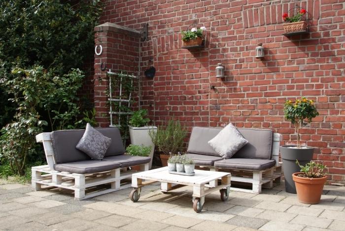 aménagement de jardin avec une déco murale en suspensions florales et lanternes sur façade en briques rouges, meubles de jardin en palettes