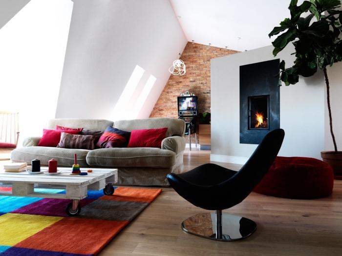 salon design moderne qui mixe les styles déco, une table basse palette blanche à roulettes joliment accentuée par le tapis milticolore