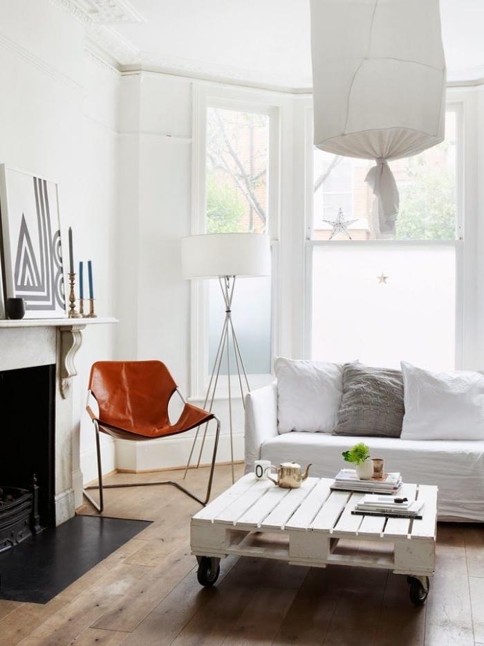 une table basse palette blanche à roulettes qui s'inscrit parfaitement dans l'intérieur blanc immaculé du salon bohème scandinave