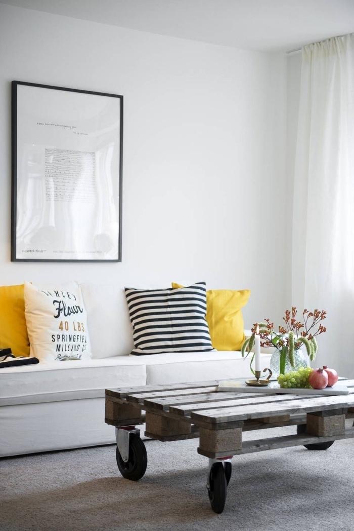 salon de style scandinave avec une table palette sur roulettes d'aspect brut industriel, réveillé par des touches de couleur