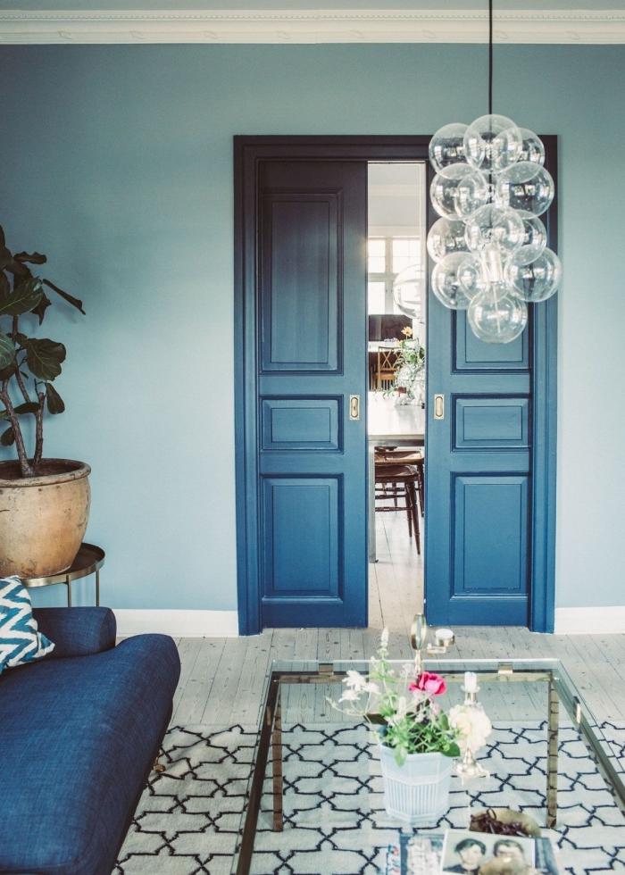 une ambiance élégante et chic dans ce salon bleu où la porte interieure a été repeinte en nuance plus foncée et profonde du bleu
