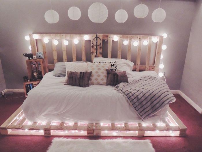 lit avec palettes perdues grand format sur sol et mur avec guirlande lumineuse