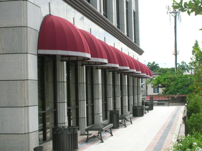 un store banne corbeille en bordeaux et en blanc, en forme semi-ronde, store banne solaire, magasin bijouterie de luxe avec trois petits bancs devant les vitrines
