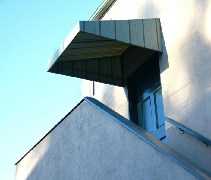 store exterieur en bleu pastel aux rayures verticales jaune et bordeaux, escalier étroit, porte bleue, garde-corps avec des poignées en bois bleu pastel