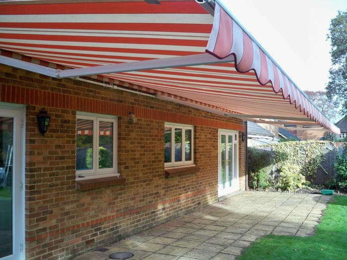 store banne en tissu rouge aux rayures verticales blanches, store banne motorisé, maison aux murs en briques oranges et marron