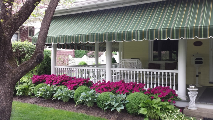 une véranda avec garde-corps et colonnes en bois peint en blanc, store banne motorisé en vert réséda et des rayures fines en blanc et jaune, jardin avec des fleurs en couleurs fuchsia et des boules vertes