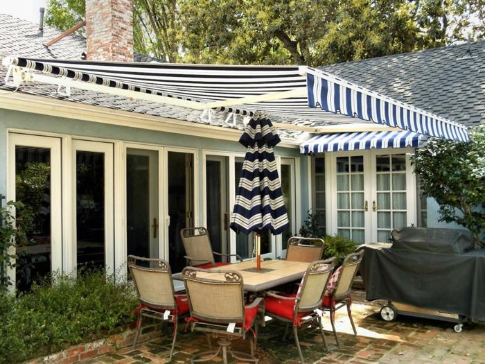 pergola, véranda, store banne electrique en tissu bleu marine avec des rayures verticales blanches, store banne sur mesure, store exterieur au-dessus d'un salon de jardin, meubles en métal clair et paille tressée