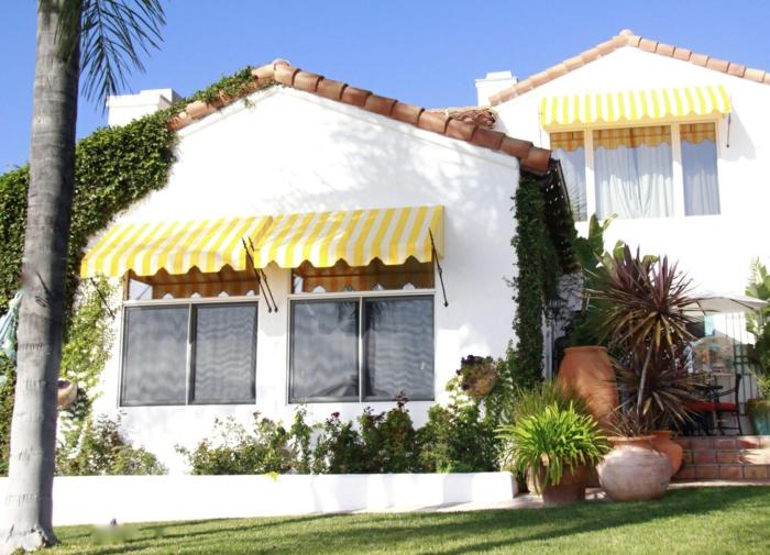 une maison de banlieue aux murs blancs, store banne en tissu jaune et rayures verticales blanches, store exterieur, store banne solaire, pelouse verte devant la maison