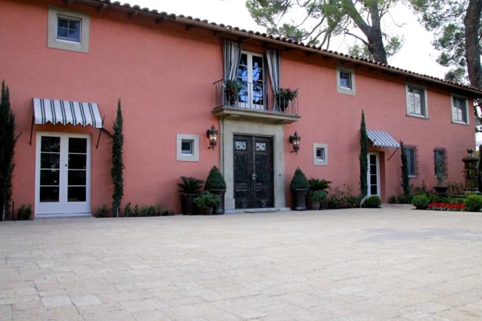 store banne solaire, store banne electrique, édifice en longueur aux murs peints en rose, toit classique, dalles carrées blanches devant l'entrée