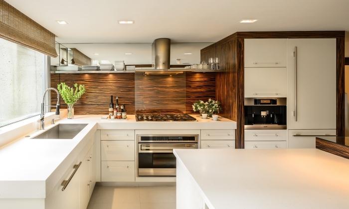 décoration de cuisine avec meubles blanc et revêtement mural en bois foncé, modèle de cuisine blanche avec finition bois