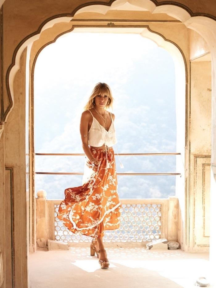 jupe taille haute longue de couleur orange à motifs fleuris blancs combinée avec sandales hautes beige et collier or boho chic