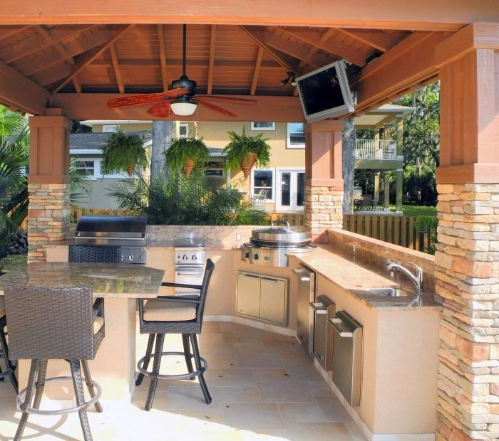 cuisine d'été en bois couverte avec toit de bois et ventilateur de plafond, aménagement cuisine d'été avec plan de travail en granite ou dekton