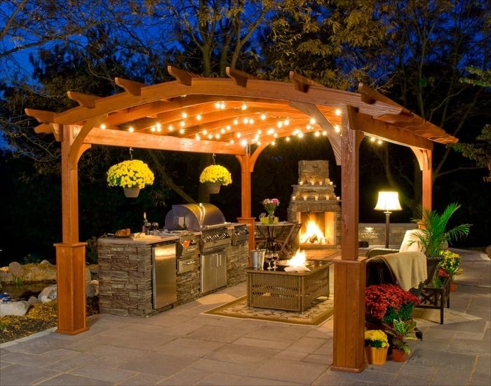 modèle de cuisine exterieure avec pergola en toit de bois décoré de guirlande lumineuse, aménagement coin culinaire de jardin avec barbecue