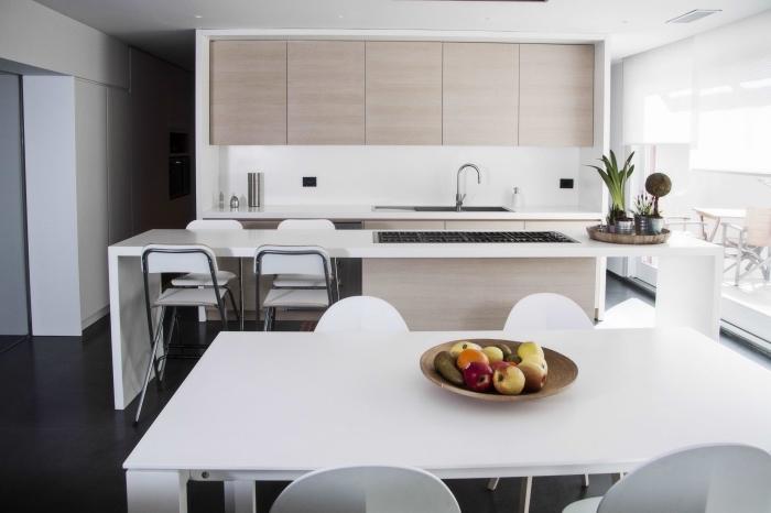 déco aux lignées épurées dans une cuisine blanche équipée avec meubles haut de bois clair sans poignées