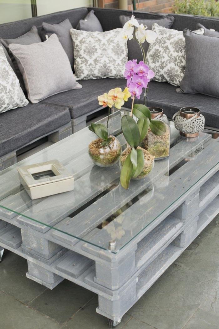 une table basse exterieur patinée grise avec un plateau en verre et une jolie déco d'orchidées en vase en verre