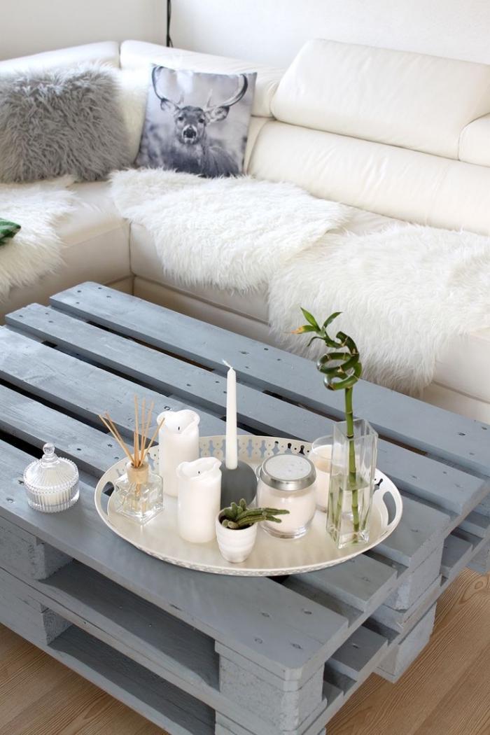 une table basse originale réalisée avec deux palettes récupérées superposées, à structure allégée , repeinte en gris pour un joli effet de contraste avec le canapé blanc