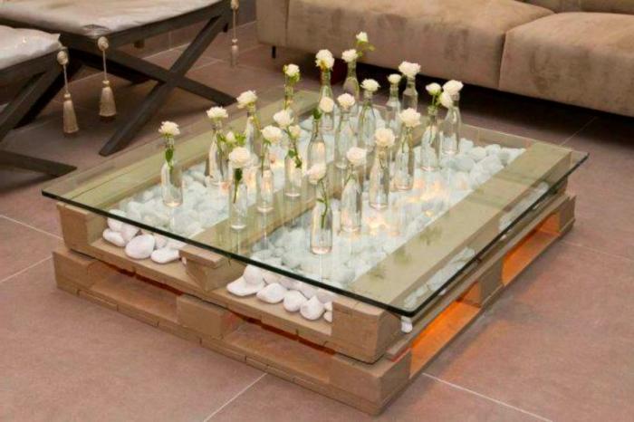 une table basse originale au design chic avec un plateau en verre et une décoration de galets et de vases soliflores