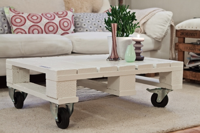 une table basse palette blanche montée sur roulette qui s'inscrit parfaitement dans l'intérieur blanc et cosy du salon