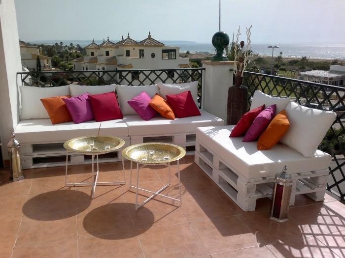 ambiance exotique sur une terrasse au carrelage de sol marron aménagée avec mobilier en palette de bois blanc