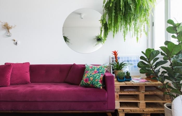 une table palette d'aspect brut posé à côté d'un canapé moderne en velours couleur rose fushia pour un joli effet de contraste dans ce salon d'ambiance tropicale