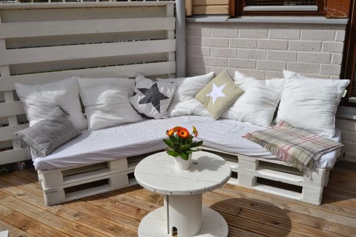 coin extérieur au plancher de bois aménagé avec meuble d'angle DIY en palettes de bois couvert de coussins avec petite table