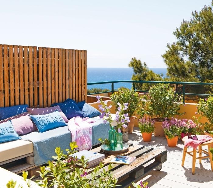 exemple de salon de jardin en palette DIY avec un canapé couvert de coussins bleu rose et une table basse