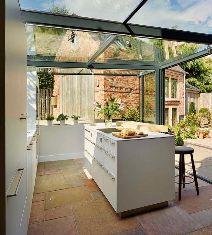 exemple d'abri cuisine extérieure en verre, modèle de cuisine ouverte avec ilot central blanc et tabourets de bar noirs