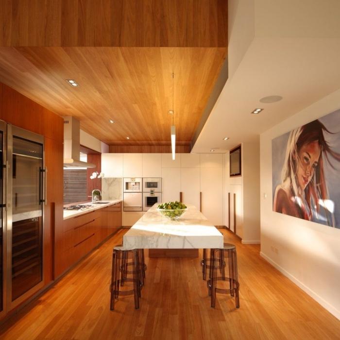 idée comment arranger une cuisine ouverte avec coin à manger, pièce au plafond et parquet bois marron avec pan de mur blanc