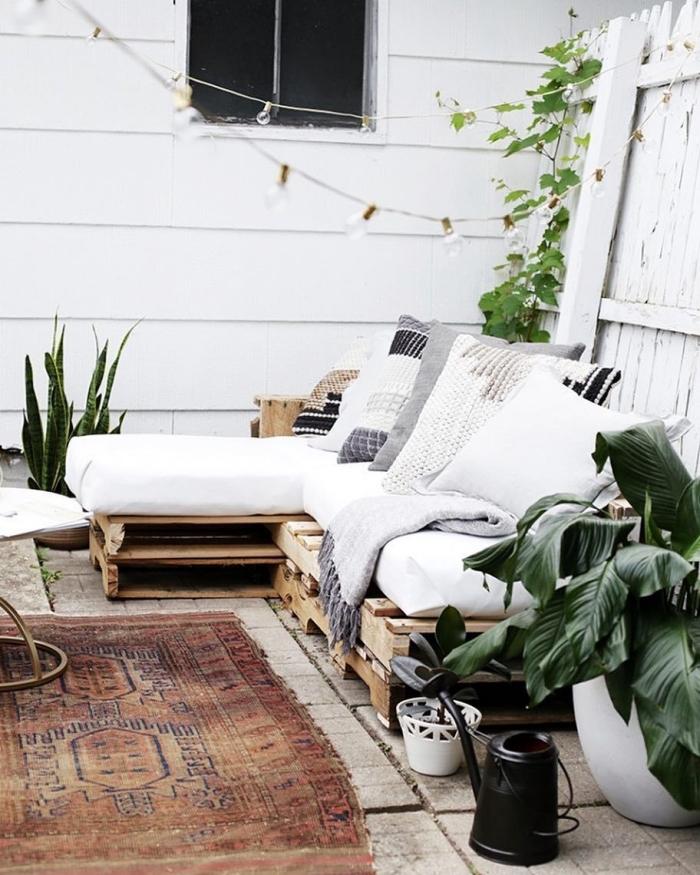 ambiance de style boho chic sur une terrasse ou déco de jardin avec meuble canapé en palette et coussins