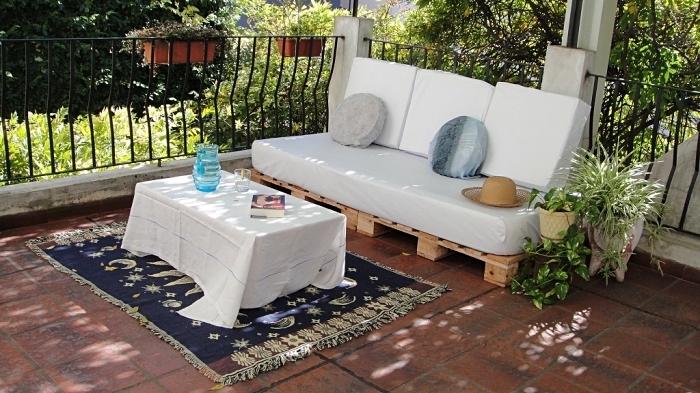 exemple salon de jardin palette avec canapé et table basse DIY couvert de nappe et coussins blancs, déco avec plantes vertes