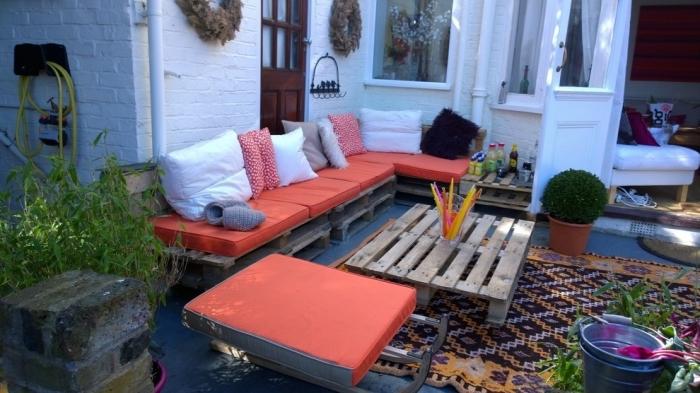 coin de repos dans le jardin avec canapé d'angle DIY en palette et table basse en bois foncé, idée aménagement extérieur