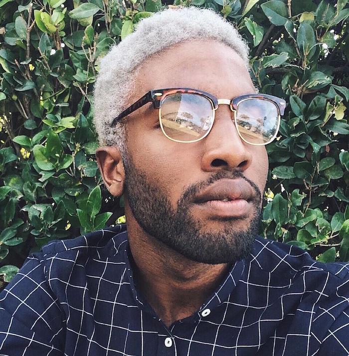 photo de teinture blond homme métisse avec cheveux crépus et barbe courte de quelques jours et chemise carreaux bleu et blanc