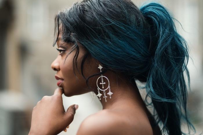 idée coiffure pour cheveux longs de base noire avec pointes colorées en bleu turquoise, modèle de boucles d'oreilles en argent