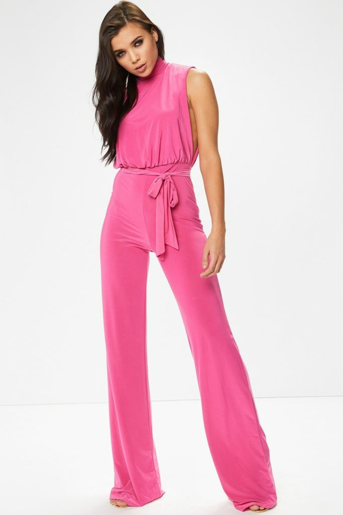 combishort mariage en rose bonbon, taille sublimée par une ceinture en tissu avec gros nœud, tissu moulant, top sans manches, bouts des pantalons longs a couvrir les talons des sandales
